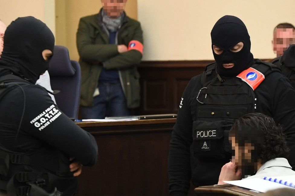 Salah Abdeslam sits surrounded by Belgian special police officers in the courtroom at the Palais de Justice courthouse in Brussels.
