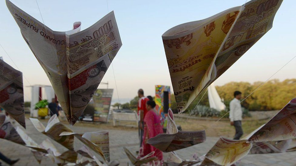 People walk past replica prints of the demonitised 500 and 1000 rupee notes as part of a street art exhibition in Mumbai