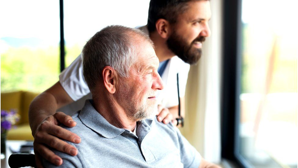 carer looks out of window with elderly man