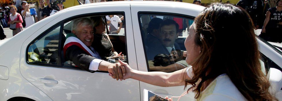 A woman shakes hands with Mexico's new President Andres Manuel Lopez Obrador as he travels in his car towards to National Palace in Mexico City