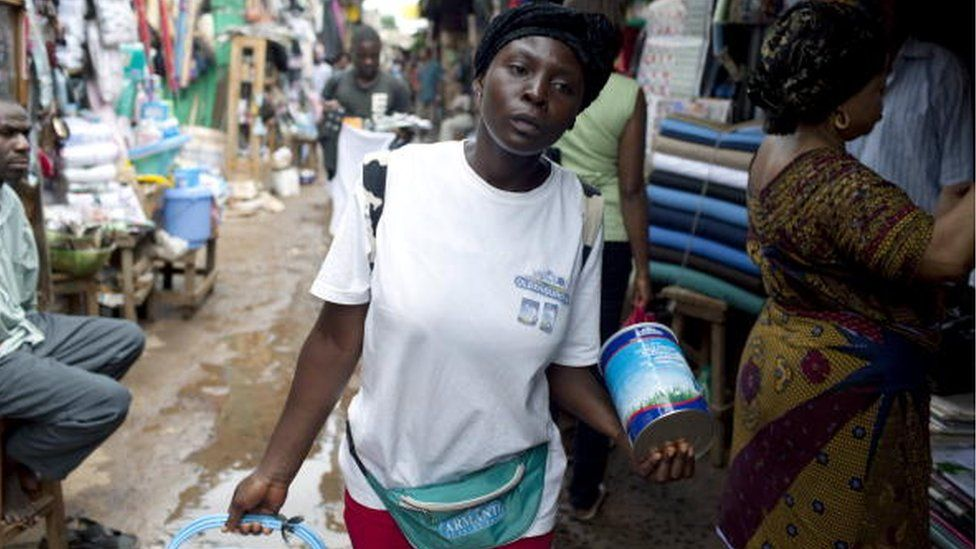 Felicity, age 20, walks in the central market selling the Oldenberger milk powder on August 8, 2009 in Bamenda, Cameroon