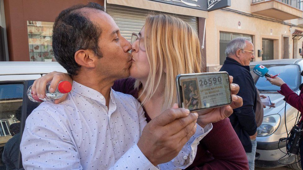 Couple Yesica Garcia (R) and Alexander Zambrano (L) celebrate at the lottery administration Virgen de La Salceda where they bought their winning ticket.