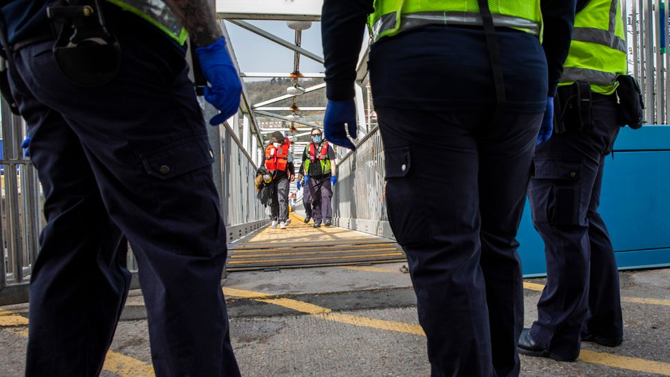 Asylum seekers arriving into Dover up the dock walkway ramp accompanied by Boarder Force officers after being on board a Boarder Force RIB boat, they were rescued in the English Channel while crossing in small inflatable dinghy on the 31st of March 2021 in Dover, Kent, United Kingdom.
