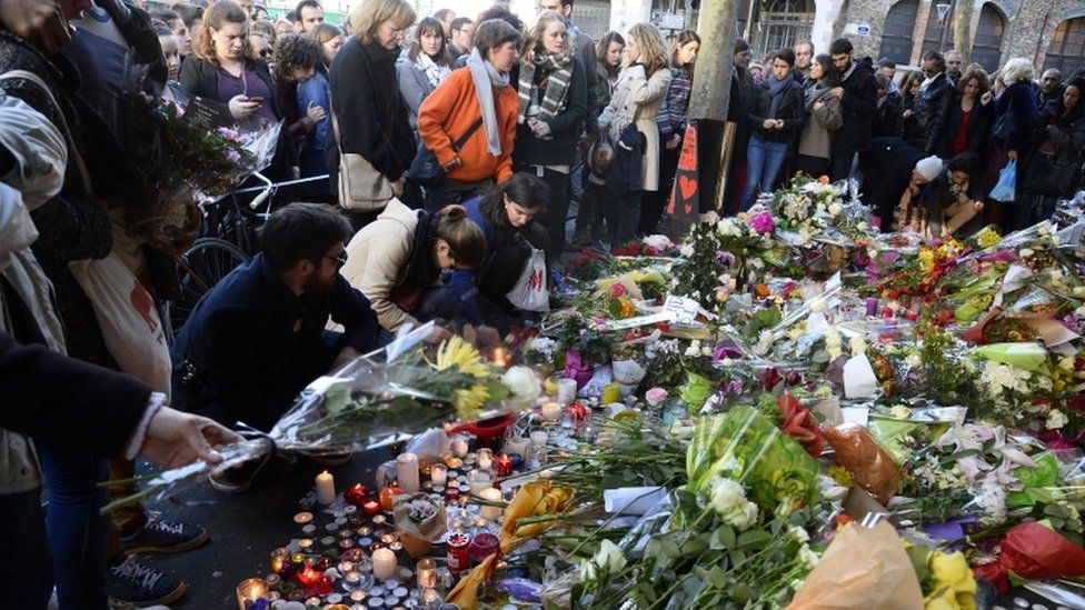 People gather at a makeshift memorial site on November 15, 2015, outside of the La Belle Equipe cafe