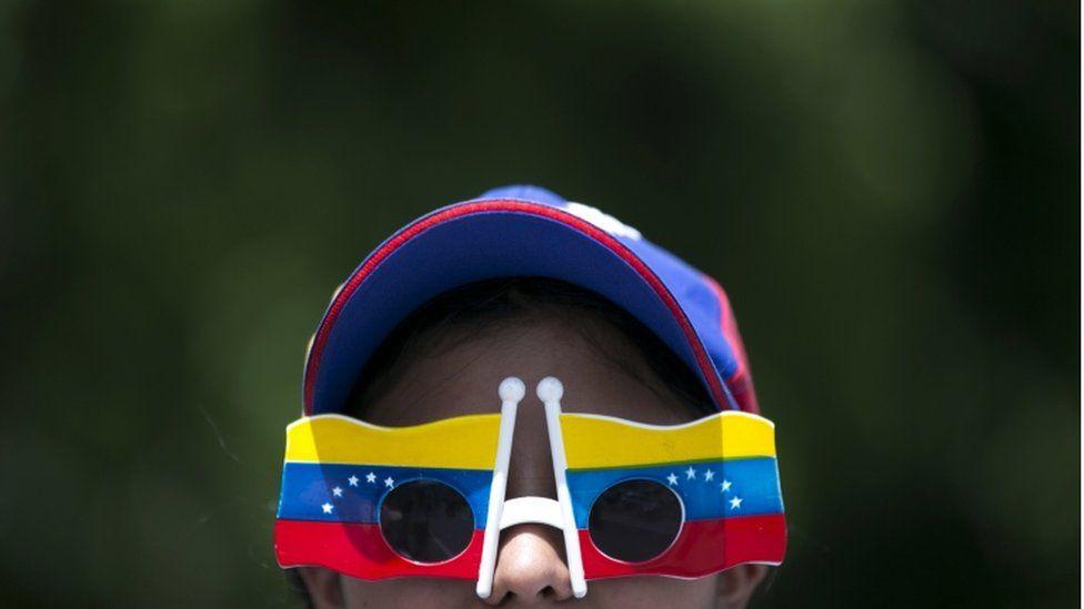 "A woman wears Venezuelan flag motif glasses during a protest demanding a recall referendum against Venezuela""s President Nicolas Maduro Caracas, Oct. 22, 2016."