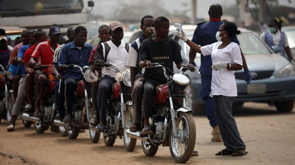 People on motorcycles temperature are measured at a border between Abuja and the Nasarawa State on March 30, 2020,