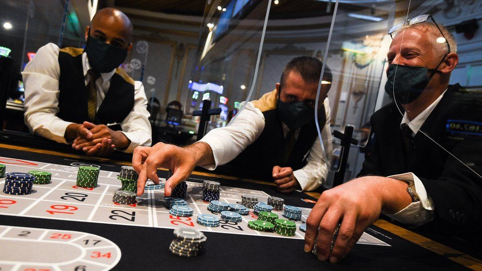 Staff wearing personal protective equipment run through a game of roulette at The Rialto casino in central London