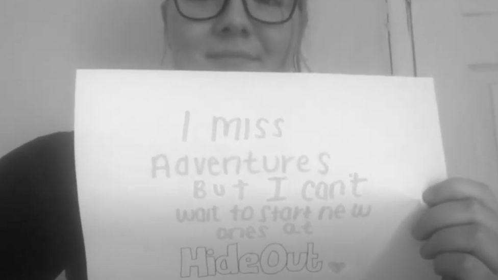 """A young person holds up a sign that says """"I miss adventures but I can't wait to start new ones at Hide Out"""""""