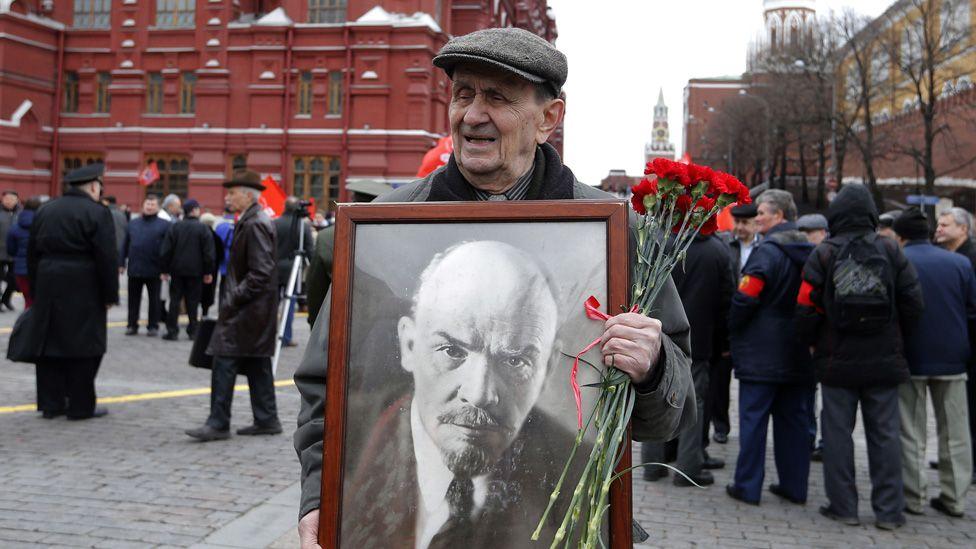 Man holds portrait of Lenin