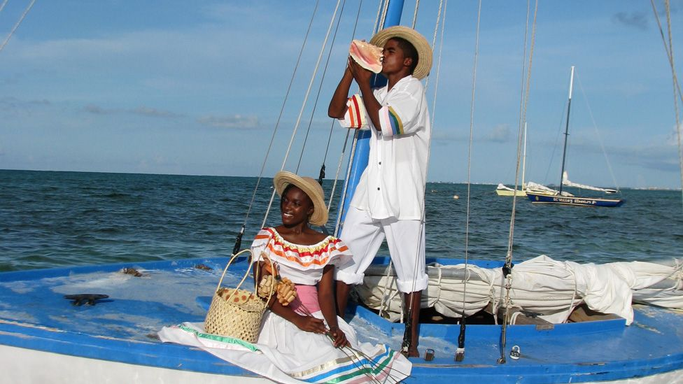 A man blows a conch while on a boat