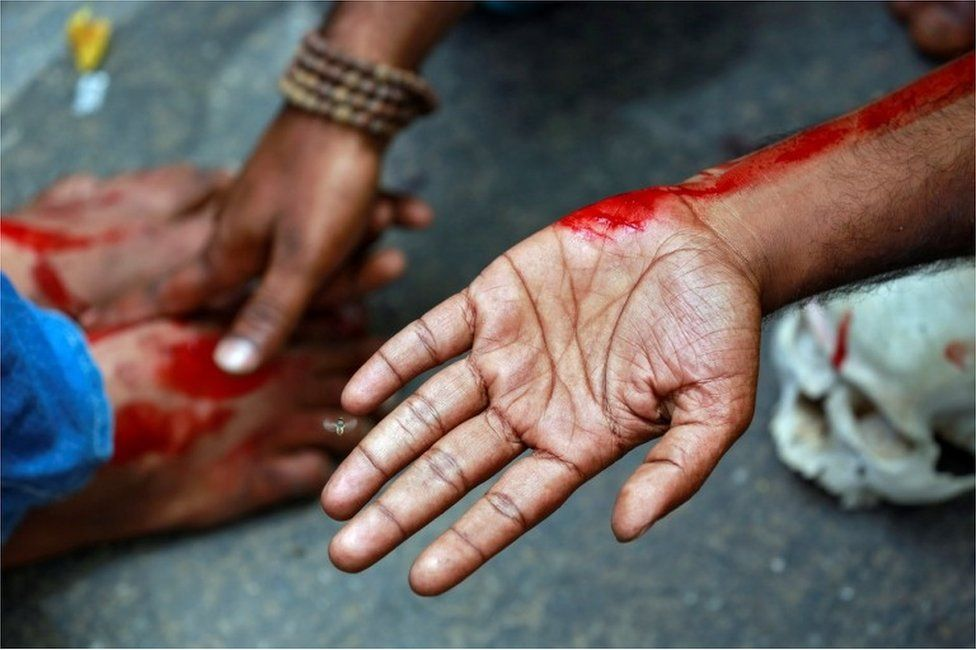 A farmer from the southern state of Tamil Nadu rubs blood on a fellow protestors feet after deliberately cutting himself with a razor blade during a protest demanding a drought-relief package from the federal government, in New Delhi, India April 7, 2017.