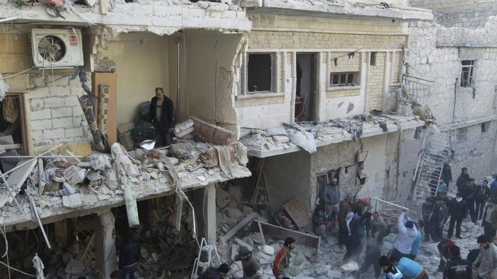Residents search for survivors after what activists say was an air raid in Aleppo, 28 December 2013