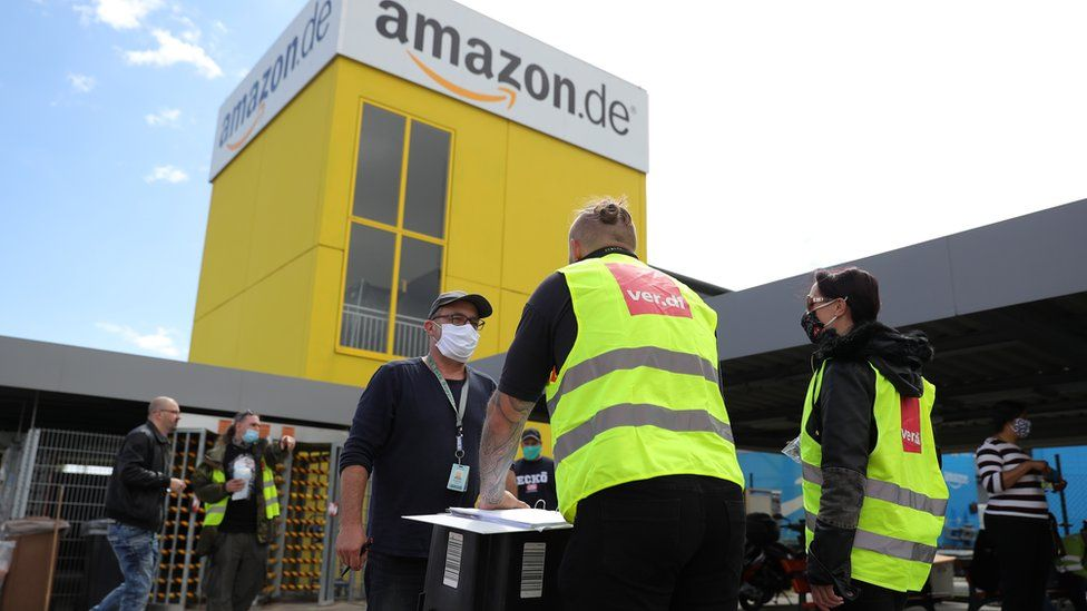 Striking Amazon employees stand outside an Amazon warehouse during the coronavirus pandemic on June 29, 2020 in Kobern-Gondorf near Koblenz, Germany