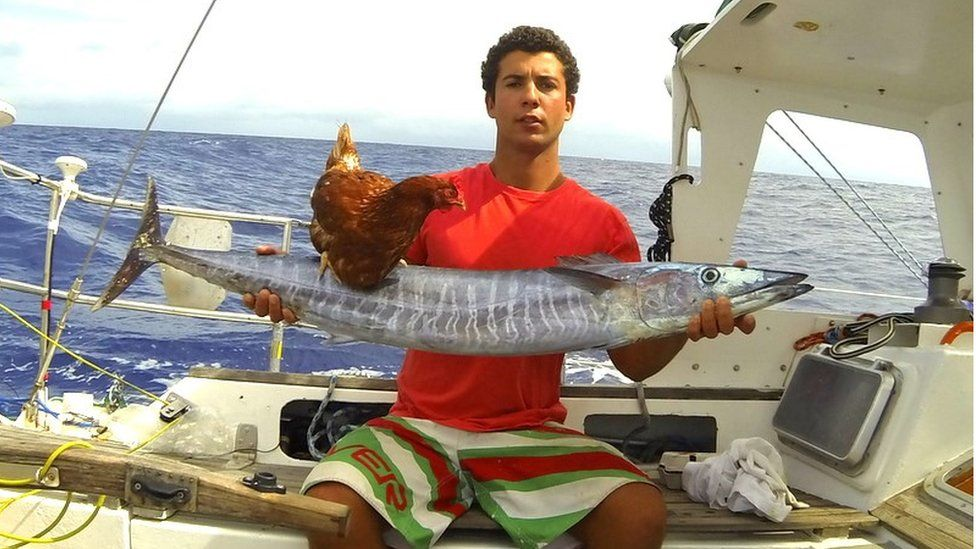 Sailor Guirec Soudee with a fish he caught, and Monique the hen standing on top of it