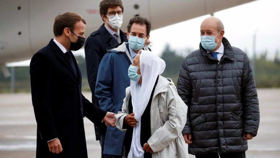French President Emmanuel Macron welcomes French aid worker Sophie Petronin who was freed from captivity in the hands of Islamist insurgents upon her arrival at the Villacoublay military airport near Paris, France October 9, 2020