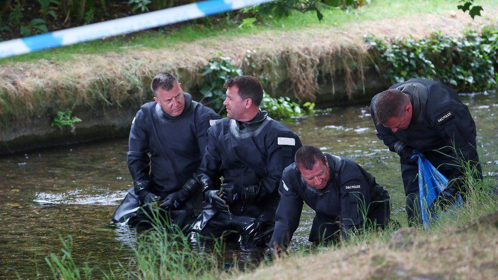 Officers searching a stream in Queen Elizabeth Gardens in July
