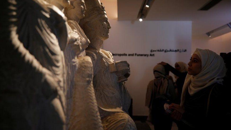 Women examine sculptures during museum reopening