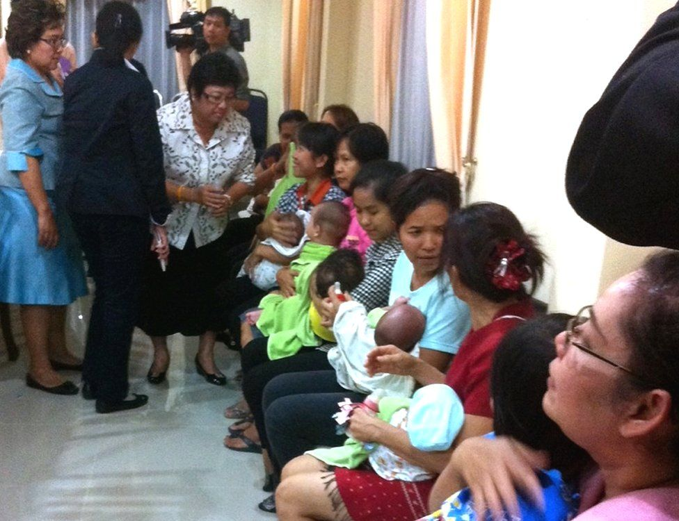 Thai nannies holding nine suspected surrogate babies after a police raid at a residential apartment on the outskirts of Bangkok, Thailand, 5 August 2014