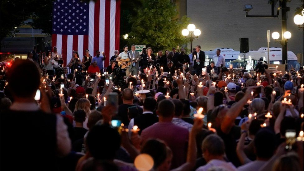 Local and state politicians and business leaders join community members for a vigil at the scene of a mass shooting in Dayton