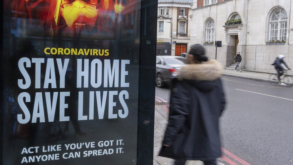 A UK government sign on a bus stop asks people to stay at home