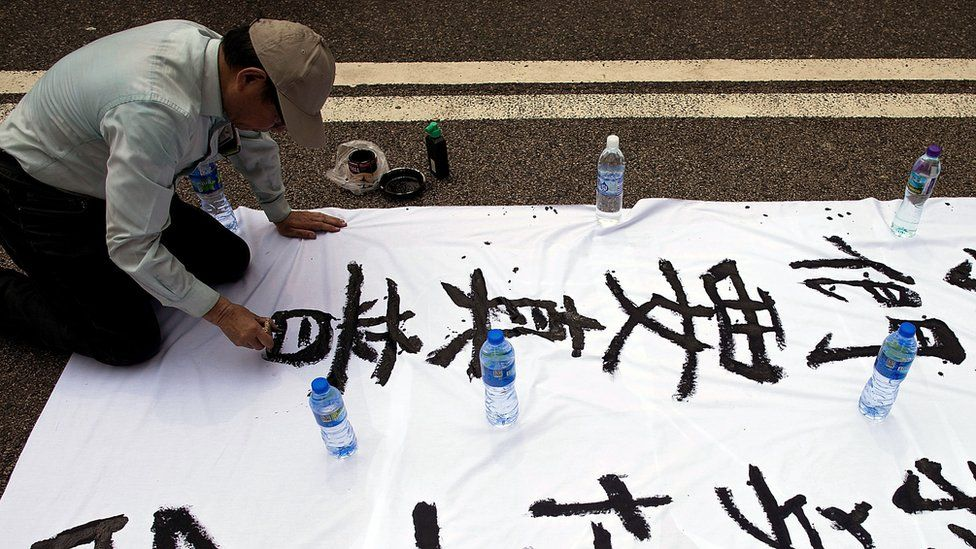A protester writes slogans in calligraphy outside of Hong Kong Government Complex on September 30, 2014 in Hong Kong