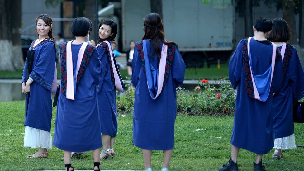 A group of students pose for photographs at a university in Beijing on June 8, 2015