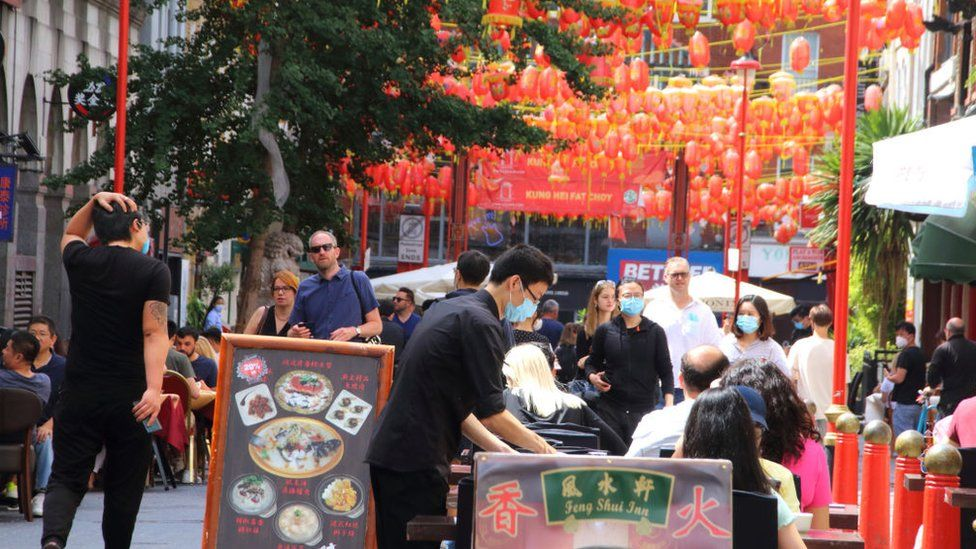 A waiter serves customers outside a restaurant in London's Chinatown during the Eat Out to Help Out scheme