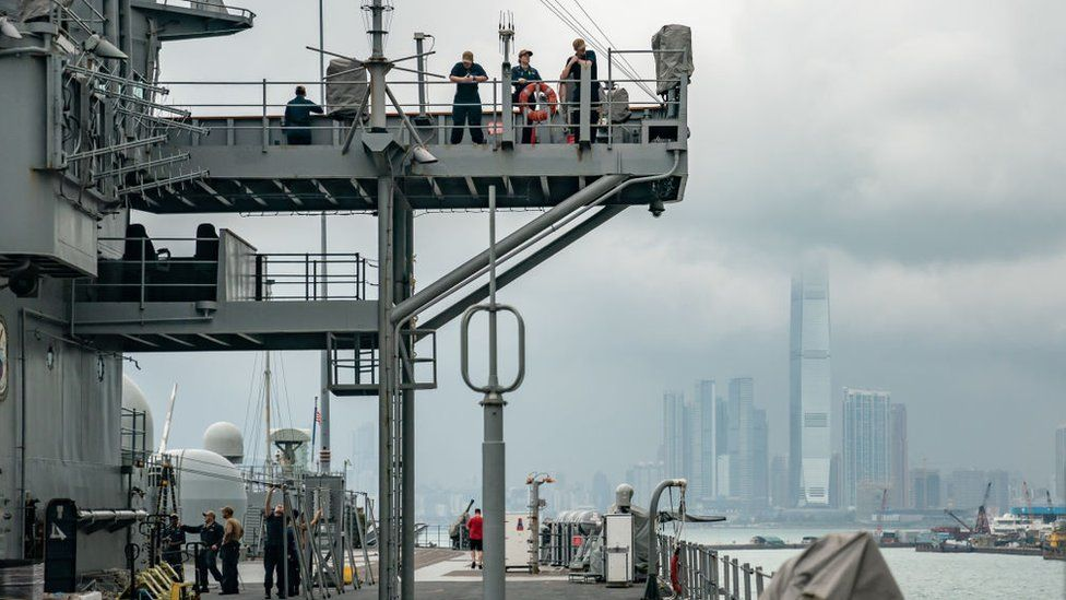 Navy crew members of the USS Blue Ridge stand on the deck as the ship is docked at a wharf during a port call on April 20, 2019 in Hong Kong