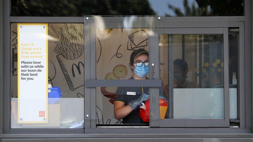A member of McDonald's staff behind a reinforced driver thru serving window