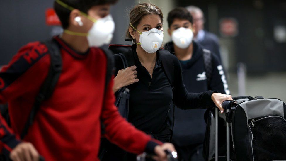 Passengers wearing face masks at an airport terminal