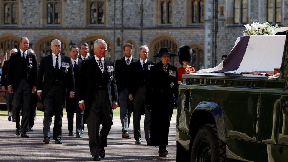 Принц Чарльз, принцесса Анна и члены королевской семьи идут за катафалком герцога на территории Виндзорского замка.