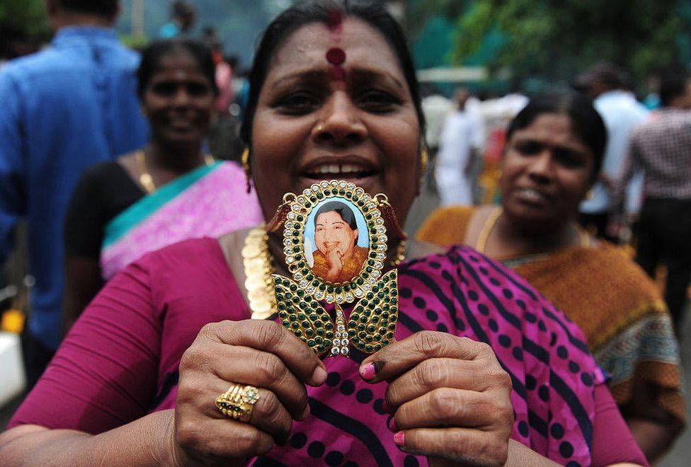 A member of the All India Anna Dravida Munnetra Kazhagam(AIADMK) party displays a pendant with the image of AIADMK leader Jayalalithaa Jayaram as they celebrate in front of her residence in Chennai on May 19, 2016.