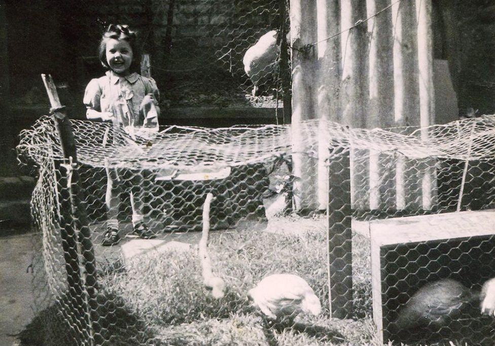 Carla Ferri as a child with chicken pen