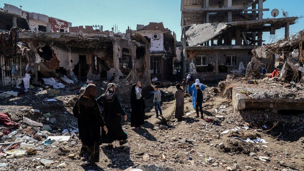 People walk past ruined houses and shops in Cizre, Turkey (8 March 2016)