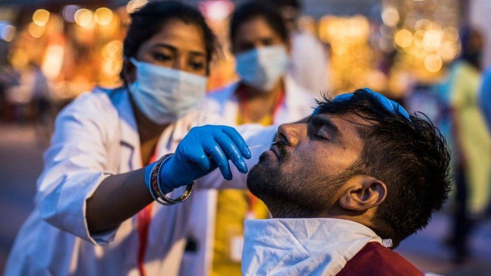 A health worker collects a nasal swab sample from a Hindu devotee to test for the Covid-19 coronavirus during the ongoing religious Kumbh Mela festival in Haridwar on April 12, 2021.