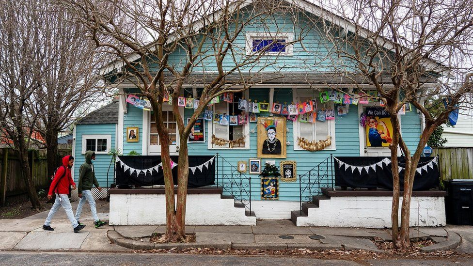 People walk past a house paying homage to influential women
