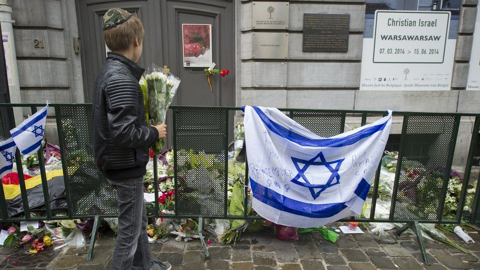 A Jewish boy stands with flowers in front of an Israeli flag and flowers laid in front of the Jewish Museum in Brussels on May 26, 2014,