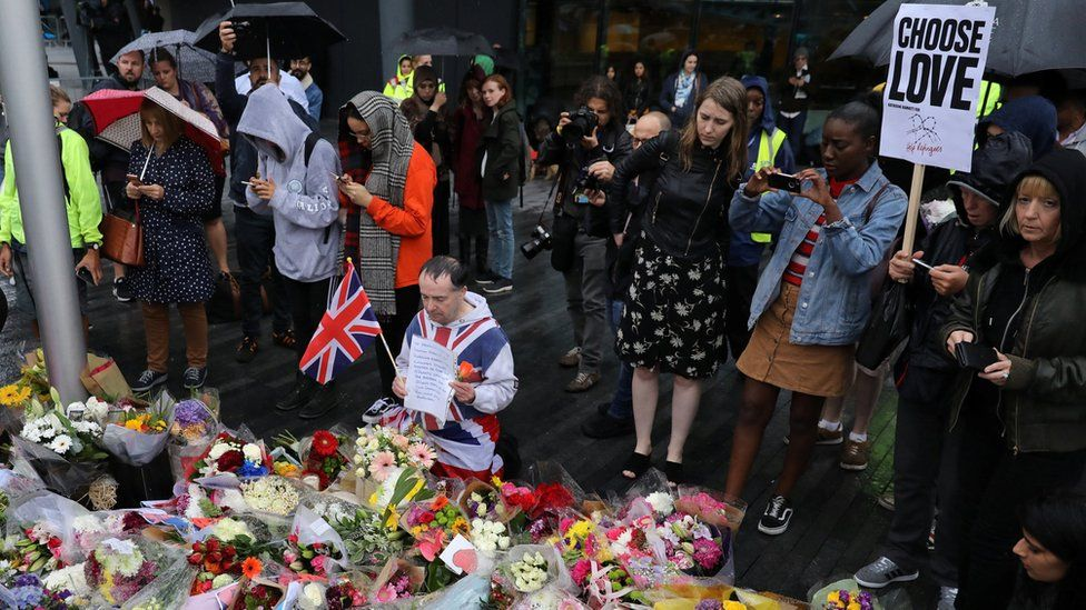 A man kneels before floral tributes after a vigil in central London