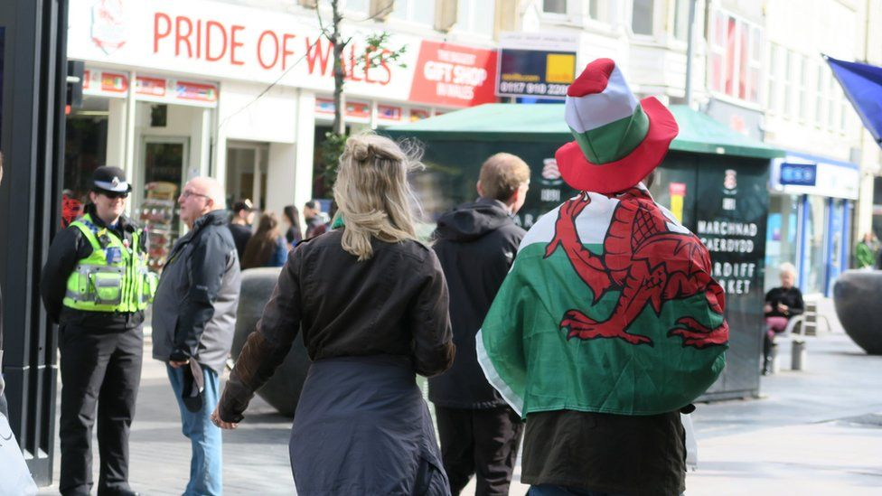 A man dressed in a Welsh flag outside the Pride of Wales shop