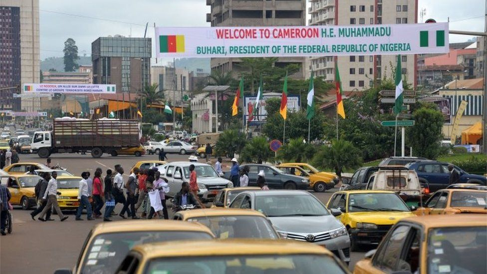 "A banner reads ""Welcome to Cameroon - Muhammadu Buhari, President of the Federal Republic of Nigeria"" in Yaounde, Cameroon, on 27 July 2015"