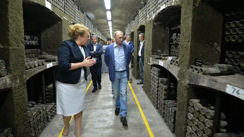 Russia's President Vladimir Putin (C) and Italy's former Prime Minister Silvio Berlusconi (unseen) examine a wine depository of Massandra winery in Yalta, Crimea (11 September 2015)