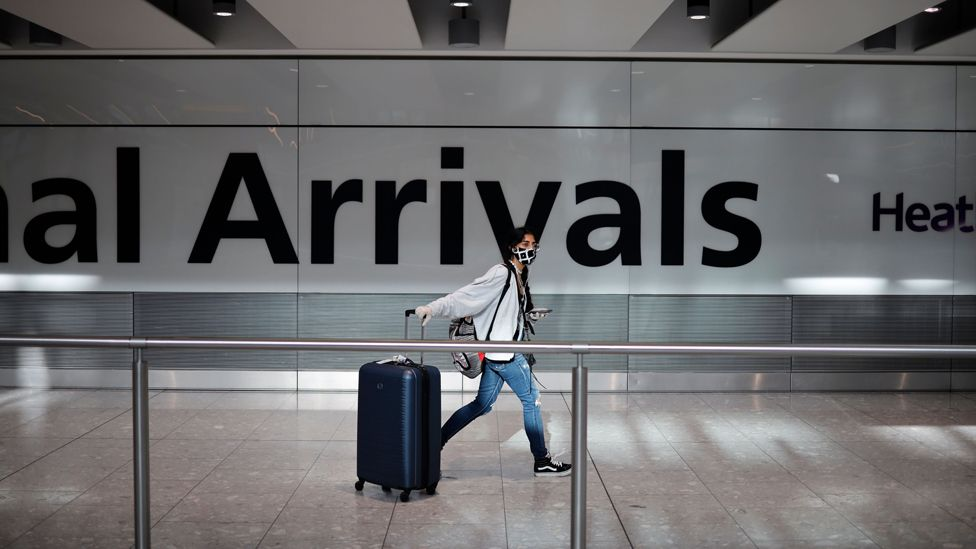 A passenger wearing a face mask as a precaution against the novel coronavirus arrive at Heathrow airport, west London,