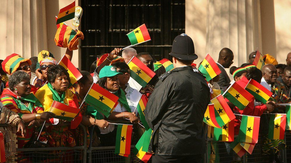 Ghanaians in London wave flags as they wait on the Mall ahead of a visit by Ghana's president to the UK - March 2007