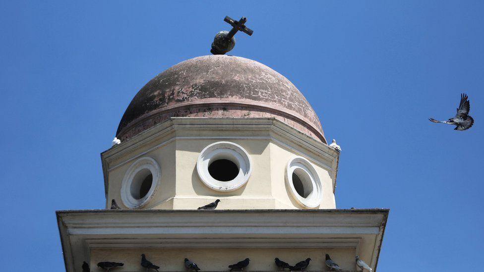 A bird flies past the bell tower of the Church of the Pantanassa
