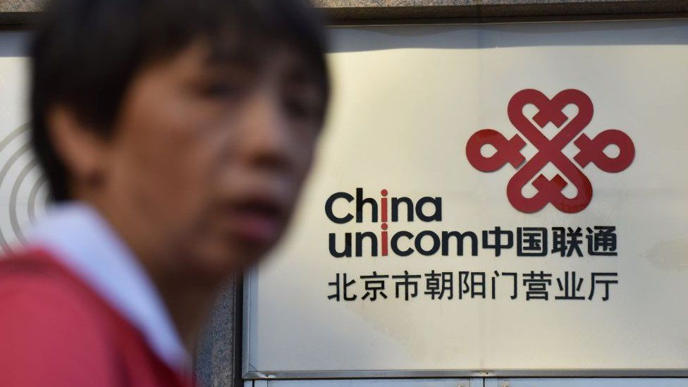 Man in soft focus in front of China Unicom sign.
