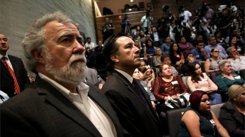 Deputy Secretary of Human Rights Alejandro Encinas Rodriguez (L) and Governor of Veracruz Cuitlahuac Garcia Jimenez (R), watch a screen in a public apology offered to relatives of five youths killed in 2016