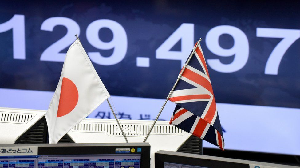 Japanese and British flags on traders' computer screens