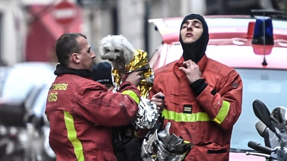 Paris firefighters carry a rescued dog wrapped in a foil blanket near the scene of the fire.