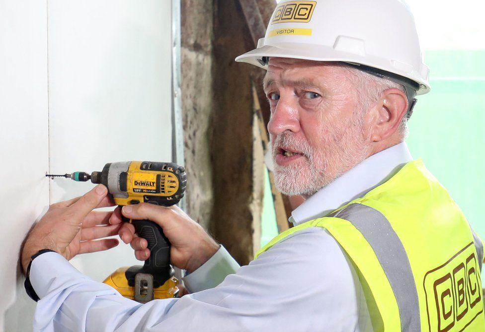 Jeremy Corbyn holds a drill.