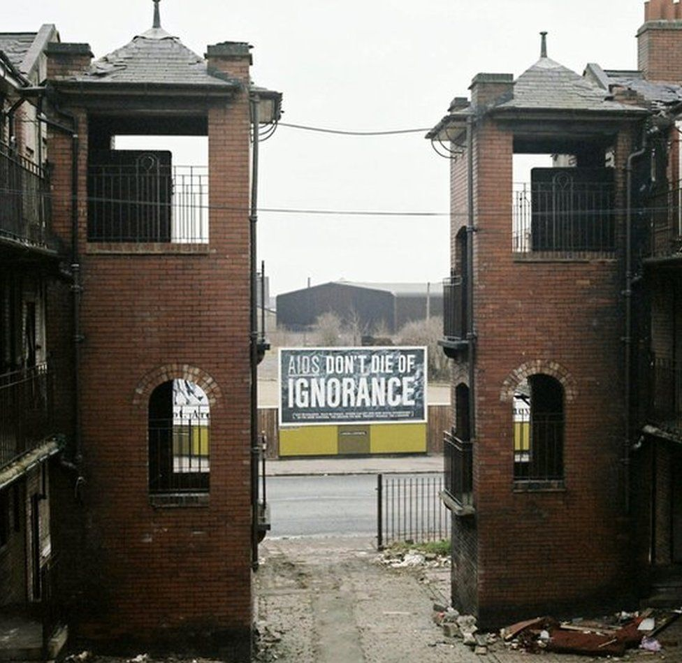 Two derelict buildings with AIDS health sign